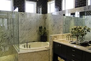 bathroom with a large sit in tub and stone surround