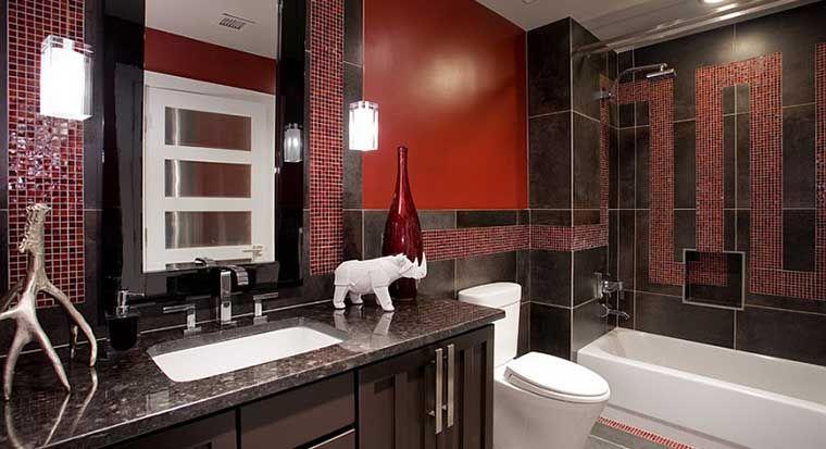 bathroom with black tile backsplash and gold walls